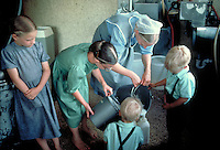 Twin boys aged four years and two girls aged 13 and 11 help their mother pour milk in the milkhouse to feed calves. Amish mother and children. New Holland Pennsylvania United States Amish farm.