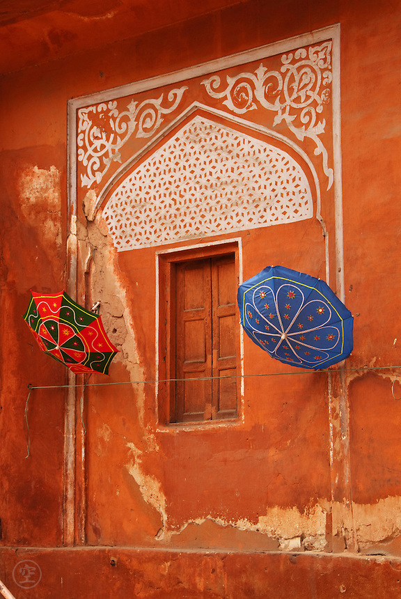 "Colourful umbrellas hang against a decorative window in the terracotta coloured walls of Rajasthan's ""Pink City"", Jaipur, India."
