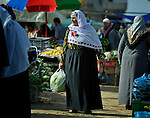 A woman shopping in the market of the Nuseirat refugee camp in the middle of the Gaza strip.  While Gazans grow much of their own food, repressive restrictions on land use imposed by the Israeli military means some food has to be imported at great cost from Egypt and Israel....