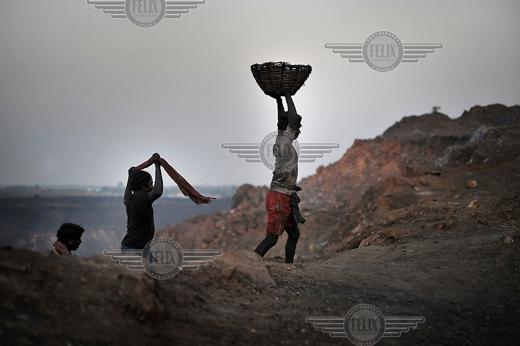Men, encrusted with coal dust after a day scavenging for coal, return home. Although technically illegal, many villages adjacent to open cast coal mines sustain themselves by collecting and selling coal scraps.