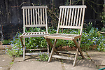 Two wooden garden chairs next to each other