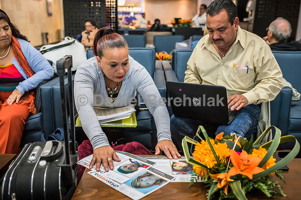 Vicky Delgadillo and Carlos Saldana pull out their pamphlets of their missing children as they work at the TAPO bus station, prior to traveling back home by bus to Xalapa, after a meeting in Mexico City on the 28th of October, 2017. Photo Daniel Berehulak for the New York Times