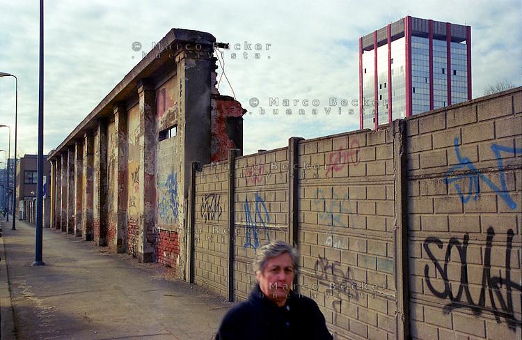 milano, quartiere lorenteggio. periferia ovest. un muro fatiscente e un palazzo per uffici --- milan, lorenteggio district, west periphery. a crumbling wall and an office building
