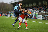 Sido Jombati of Wycombe Wanderers challenges Craig Mackail-Smith of Luton Town during the Sky Bet League 2 match between Wycombe Wanderers and Luton Town at Adams Park, High Wycombe, England on 6 February 2016. Photo by David Horn.