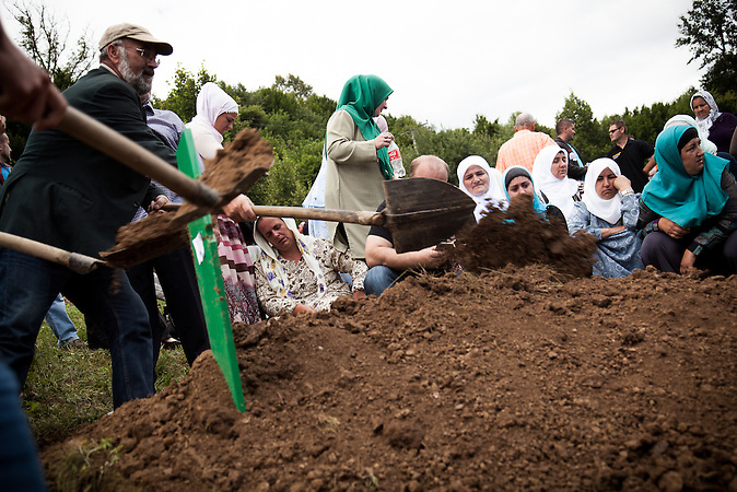 A woman is fainting during the burial of a close relative at the 19th anniversary of the Srebrenica genocide.