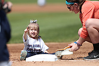 Child helps clean the bases in between innings during the Midwest League baseball game on April 26, 2017 at Fifth Third Ballpark in Comstock Park, Michigan. West Michigan defeated Fort Wayne 8-2. (Andrew Woolley/Four Seam Images)