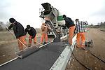 CULEMBORG - In Culemborg werken medewerkers van Hewi Beton met printbeton aan de middenberm van de door aannemersbedrijf Kroeze gebouwde rondweg bij industrieterrein Pavijen. Om het beton een steenuitstraling te geven is het met kleurstof in de betonmolen eenvoudigweg zwart gemaakt en krijgt het na egaliseren met poeder en reliëfplanken een stenen uiterlijk. Hetzelfde materiaal wordt ook regelmatig in diverse kleuren gebruikt voor rotondes. COPYRIGHT TON BORSBOOM..