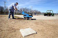 NWA Democrat-Gazette/DAVID GOTTSCHALK Marshall Wood (left), with the city of Fayetteville Parks and Recreation Department, uses a sod cutter Monday, March 5, 2018, to remove growth from the edge of the infield on Field 8 at Walker Park in Fayetteville. Wood was working with Justin Parker, also with the city, on the fields at the park. Walker Park was the second park added to the city parks system in 1949.