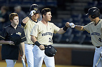 Chris Lanzilli (24) of the Wake Forest Demon Deacons bumps fists with teammate D.J. Poteet (4) after hitting a 2-run home run against the Liberty Flames at David F. Couch Ballpark on April 25, 2018 in  Winston-Salem, North Carolina.  The Demon Deacons defeated the Flames 8-7.  (Brian Westerholt/Four Seam Images)