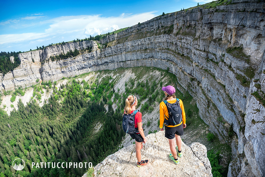 Trail running tour in the Jura Mountains of Switzerland. The Jura are an old, small mountain group in northwest Switzerland. Two runners at the Creux du Van, a large rocky cirque.