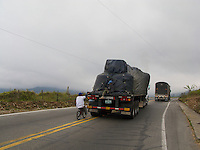 Kids hitching a ride on their bicycle from the back of a semi-truck - Colombia