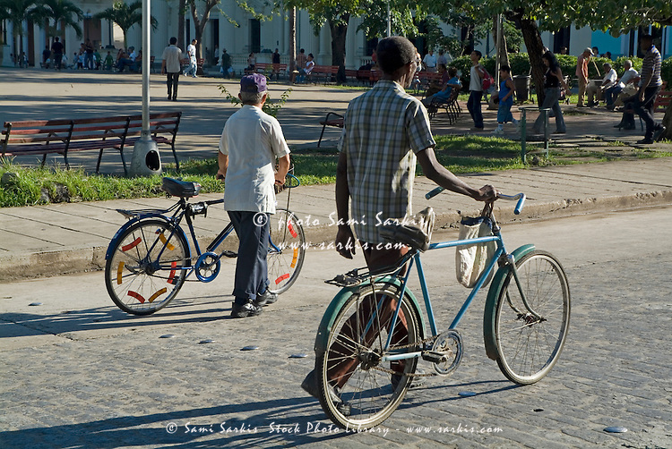 Two men walking with their bikes alongside Parque Vidal in Santa Clara, Villa Clara, Cuba.