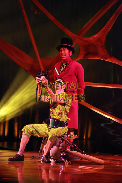 Artists from Cirque Du Soleil ; Totem perform at the Royal Albert Hall, London, England..January 4th, 2012.stage performance circus costume show atmosphere gv general view full length performers clown yellow sunglasses shades tourist camera sitting  .CAP/JEZ  .©Jez/Capital Pictures.
