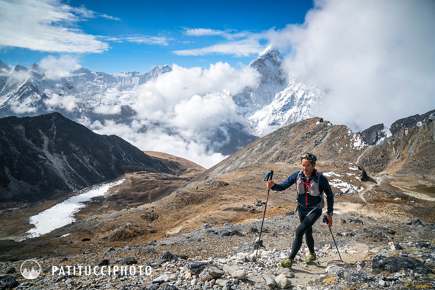 A trail runner walking up the first pass, Kongma La, above Chukhung while starting the 3 Passes tour, with a view of Ama Dablam in the background. Khumbu Valley, Nepal.