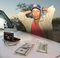Victoriano Jimenez Ramirez, 30, of Sonora, Mexico, stands next to a  Tohono O'odham Police Department jeep with his  hands up after being caught outside of Sells for crossing the border illegally. He said he was traveling with four other undocumented immigrants who fled into the desert. Photo by Pat Shannahan