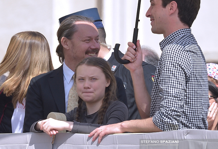 Pope Francis greets Swedish teenage environmental activist Greta Thunberg (R) during a weekly general audience at Saint Peter's square on April 17, 2019