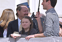 Pope Francis greets Swedish teenage environmental activist Greta Thunberg (R) during a weekly general audience at Saint Peter's square on April 17, 2019