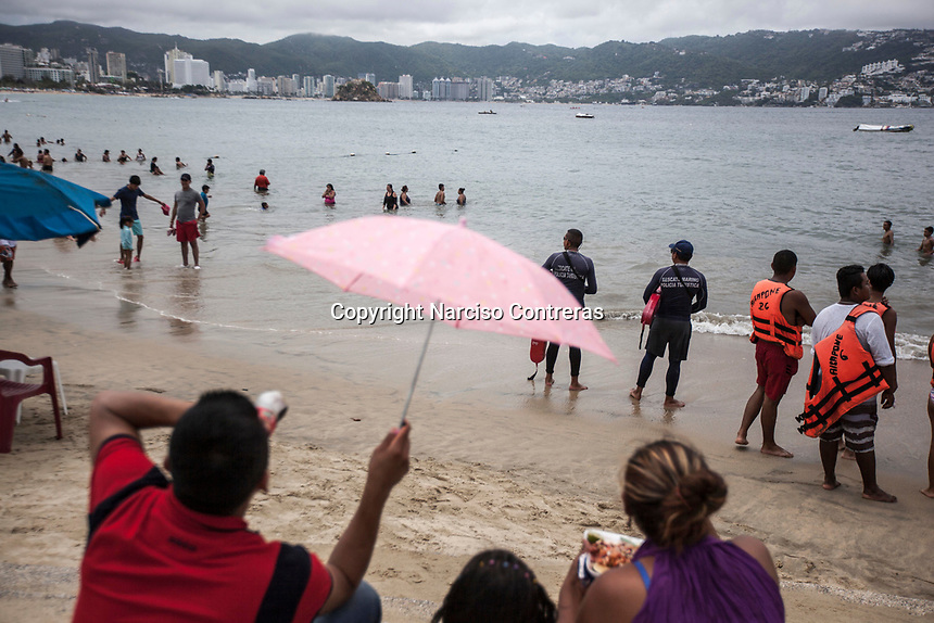 """June 16, 2018: Tourist police keep watching as beach goers and visitors arrive to """"Hornos"""" beach in Acapulco, Guerrero. A juncture of security forces, among them military, marines, federal police and local police joined under one-command to fight crime violence in the once-glamorous resort destination."""
