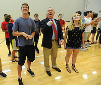 NWA Democrat-Gazette/ANDY SHUPE<br /> Jeff Long (center), athletics director at the University of Arkansas, acknowledges his daughter in the stands Wednesday, Sept. 2, 2015, while preparing to call the Hogs after speaking to a group of juniors at Fayetteville High School. Long spoke during students' seventh-period advisory period about his career as a student, as a coach and athletics director, encouraging students to pursue their dreams and their education.