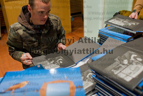 Nature photographer Bence Mate from Hungary signs his wildlife photography book during a press conference in Budapest, Hungary on December 12, 2011. ATTILA VOLGYI