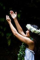 Beautiful Hawaiian woman wearing a haku and maile lei raises her hands in hula motion
