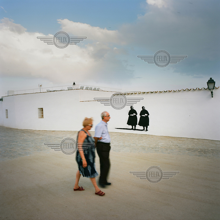 An elderly couple walk past a graffiti picture of a pair of black clad women.