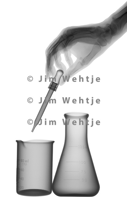 X-ray image of science glassware with hand (black on white) by Jim Wehtje, specialist in x-ray art and design images.