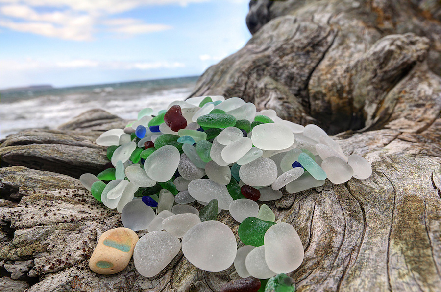 Beach glass piled on driftwood, North Beach, Port Townsend, Jefferson County, Washington State, USA