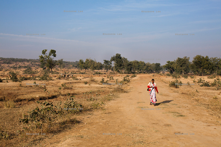Junior community reporter Sunita, 22, walks to a remote village to distribute this week's Khabar Lahariya newspapers and interview villagers in Chitrakoot, Uttar Pradesh, India on 5th December 2012. Sunita and her husband, now sick with TB and unable to work, were estranged from their families because they married against the family's wishes, so Sunita, who had finished her high-school education, supports her husband on the income she makes as a journalist. She makes about 4500 rupees a month. Photo by Suzanne Lee for Marie Claire France.