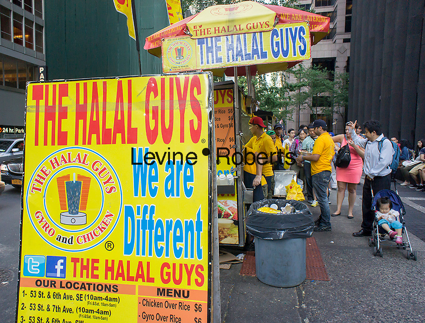 The popular Halal Guys food cart on Sixth Avenue and West 53rd Street in New York on Monday, June 16, 2014. The mini-industry of middle-eastern food, which already has five locations and permanent restaurant set to open shortly, has sign a deal with Fransmart, a firm that advises restaurants on franchising. Fransmart worked with Five Guys Burger and Fries which grew to over 1200 locations. (© Richard B. Levine)