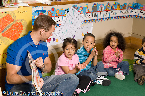 Education preschoool children ages 3-5 circle time male teacher reading book with hand gestures horizontal