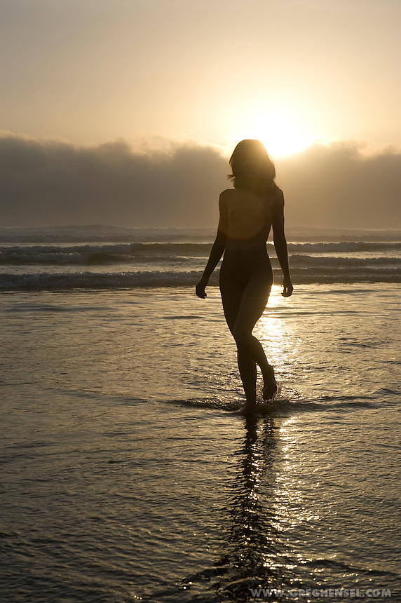 Silhouette of a nude woman walking along the beach at sunset. Spring time near the town of Lincoln City, Oregon.