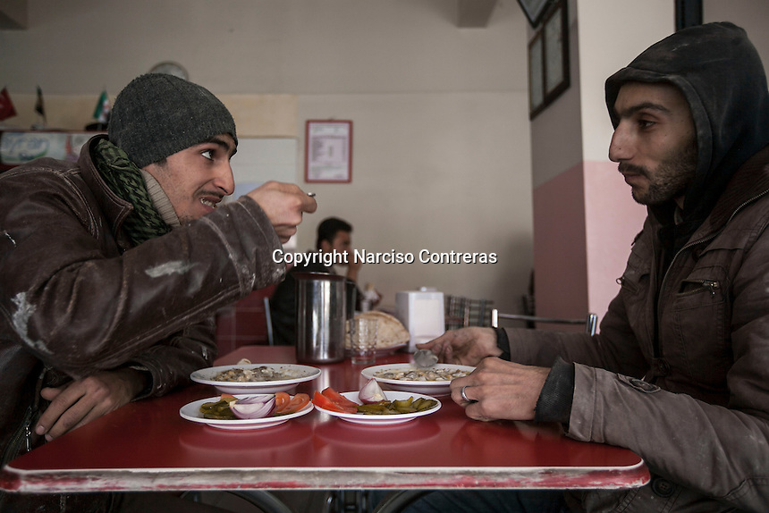 February 13, 2016: Yusuf Oso, 30 years-old (right) and Nadjmahdin Sehen, 21 years-old (left) are seen in a restaurant during a lunch break in the downtown of Gaziantep. Yusuf and Nadjmahdin, Syrian kurds from Aleppo are two among of the thousands of working class Syrian nationals that fled into Turkey during the war and now await for the war to end in order to return to their homeland.