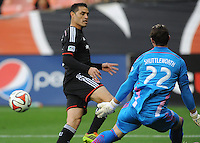 Washington, D.C.- March 29, 2014. Fabian Espindola (9) of D.C. United goes against Bobby Shuttleworth (22) of the New England Revolution. D.C. United defeated the New England Revolution 2-0 during a Major League Soccer Match for the 2014 season at RFK Stadium.