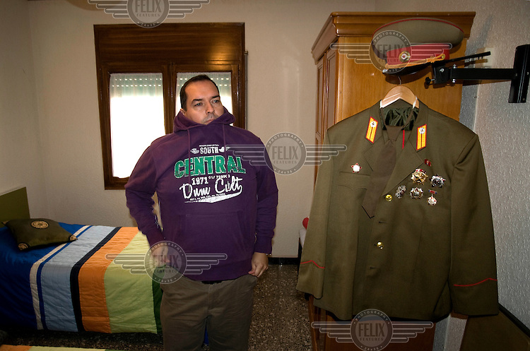 A portrait of Alejandro Cao de Benos, photographed in the village of Salomo in northeast Spain standing next to his uniform. As a Korean-Spanish communist, Alejandro is the president of the Korean Friendship Association (KFA) and has been an advocate of the Democratic People's Republic of Korea (North Korea) since 1990. His Korean name is Zo Sun-il (Korea is One) and he works as an honorary Special Delegate of the DPRK's Committee for Cultural Relations with Foreign Countries - a North Korean government spokesman in Europe.