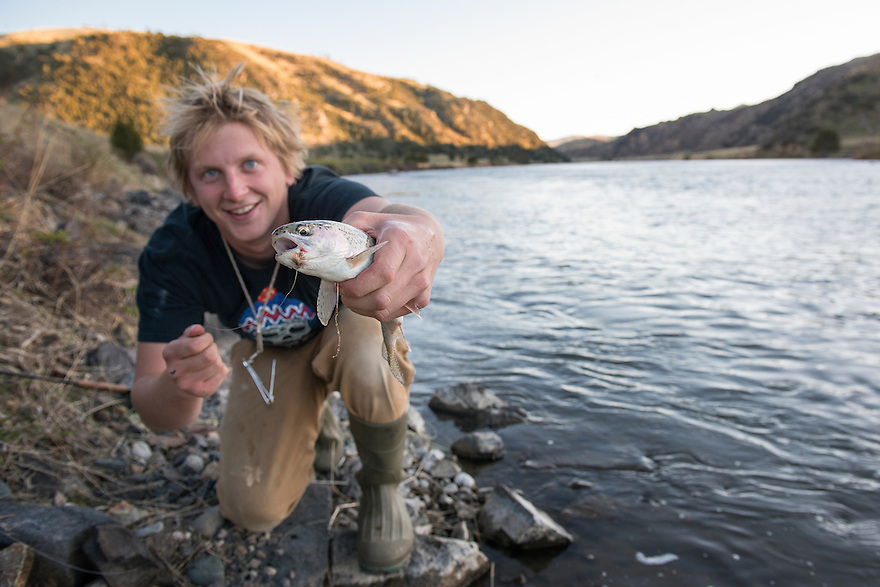 Logan Burgess holds a rainbow trout that fell for an Elk Hair Caddis pattern on the Madison River near Black's Ford fishing access site on Monday evening.