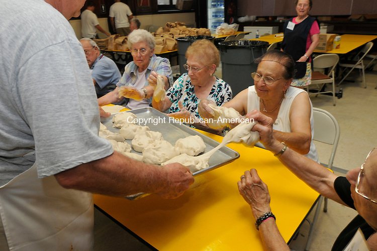 WATERBURY, CT-15 JULY 2010-071510IP03- (from right) Teri Laskarzewski, Maria Daversa, Rosalie Pontelandolfo and Louise Sticco grab dough to stretch it out for fried dough during the Our Lady of Mount Carmel Feast in Waterbury on Thursday. Fried dough is a big seller at the festival and 3,500 lbs. of dough are used throughout the four-day event to make it. The festivities at Our Lady of Mount Carmel Church, which include food, live entertainment, and kids' activities, will run through Sunday. <br /> Irena Pastorello Republican-American