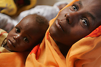 Hashania Abakar Ahmed accompanies her child to  the Oure Cassoni refugee camp hospital in Chad on Dec 31 2004. hundreds of refugees from northern Darfur arrived outside the camp and are still waiting for months to be registrated and to get help form the UNHCR mission.