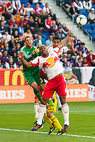 Jamison Olave (4) and Tim Cahill (17) of the New York Red Bulls collide with Columbus Crew goalkeeper Andy Gruenebaum (30). The New York Red Bulls and the Columbus Crew played to a 2-2 tie during a Major League Soccer (MLS) match at Red Bull Arena in Harrison, NJ, on May 26, 2013.