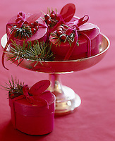 Spruce adds the final festive touch to a collection of tiny gift boxes decorated with red berries