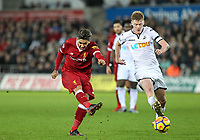 Roberto Firmino of Liverpool hits a shot past Sam Clucas of Swansea City during the Premier League match between Swansea City and Liverpool at the Liberty Stadium, Swansea, Wales on 22 January 2018. Photo by Mark Hawkins / PRiME Media Images.