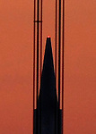 The cables of the Golden Gate Bridge frame the Transamerica pyramid during sunrise as seen from the Marine headlands, Sausalito, California.