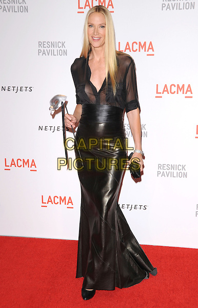 "KELLY LYNCH .at LACMA's ""The Unmasking"" The Lynda & Stewart Resnick Exhibition Pavilion Opening Gala at The Los Angeles County Museum of Art in Los Angeles, California, USA, September 25th 2010..full length black sheer shirt see thru through leather shiny long maxi dress skirt mask clutch bag     .CAP/RKE/DVS.©DVS/RockinExposures/Capital Pictures."
