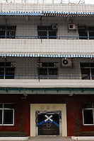 "Dingfu Factory in Houjie Town, Dongguan, China. The sign outside the factory that made shoes for Zara and Nine West amongst others, reads that the ""Dongguan People's Court have closed the factory"". As the economy changes and Chinese labour gets more expensive, factories are closing leaving ghost towns behind them..20 Dec 2007"