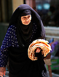 An Iranian woman walks along Imam Khomeini Street in Yazd, carrying the ubiquitous flatbread which is served at every meal.