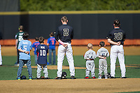 Johnny Aiello (2) and Nate Mondou (10) of the Wake Forest Demon Deacons are joined on the field by several youth baseball players for the National Anthem prior to the game against the Florida State Seminoles at David F. Couch Ballpark on April 16, 2016 in Winston-Salem, North Carolina.  The Seminoles defeated the Demon Deacons 13-8.  (Brian Westerholt/Four Seam Images)