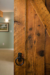 A sliding door made from reclaimed barn wood adds a touch of history to a newly-remodeled basement. This image is available through an alternate architectural stock image agency, Collinstock located here: http://www.collinstock.com
