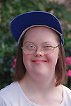 Portrait of teenage girl with Downs Syndrome wearing baseball cap smiling.  MR