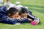 El Segundo, CA 09/27/13 - Two El Segundo cheerleaders watch a video before the start of a game,