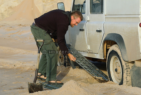 Africa, Mauritania, Sahara Desert, nr. Nouadhibou. Using sand channels to recovering a stuck Land Rover Defender TD5 Station Wagon while driving on the beach along the coastal piste from Nouakchott to Nouadhibou through the nature reserve Parc National du Banc D'Arguin in Mauritania. --- No releases available. Automotive trademarks are the property of the trademark holder, authorization may be needed for some uses.